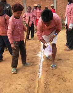 Les enfants d'Akany Aina marquent les limites du terrain de basket avec la pierre blanche