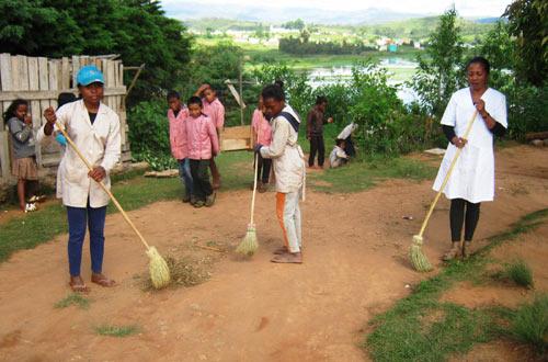 Enfants, enseignants et animateurs, tous manient le balai pour nettoyer la cour de récréation de l'école Akany Aina d'Ambatolampy à Madagascar
