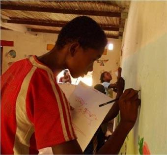 Les enfants de l'école d'Ambodirafia peignent une grande frise sure les murs de leur école à Madagascar