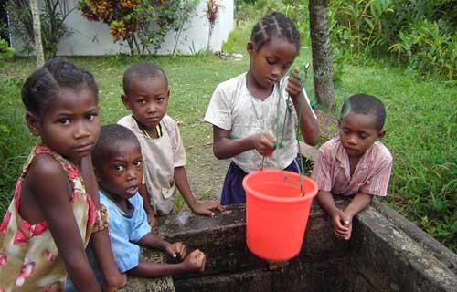 Enfants lavant leur assiette au puits de l'école d'Ambodirafia