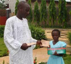 Un jeune orphelin au Bénin lisant une lettre de sa marraine