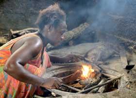 Femme Pygmée rallumant le feu