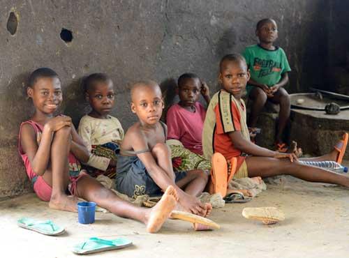 Les jeunes Pygmées bavardent tranquillement dans la cuisine