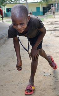 Un enfant Pygmée Bagyeli du Foyer de Bipindi joue aux billes