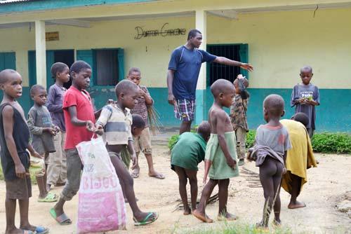 Rammasage des papiers dans la cour du Fondaf par les enfants Pygmées Bagyeli de Bipindi au Cameroun