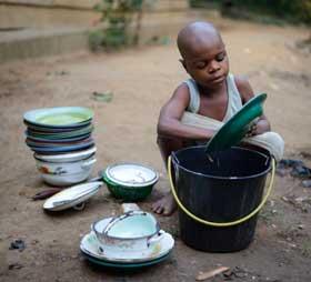 Enfant Pygmée du Cameroun lavant la vaisselle
