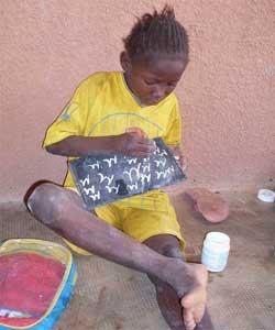 Petite écolière burkinabè écrivant sur son ardoise