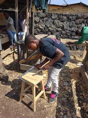 Construction d'un tabouret par un enfant soldat démobilisé en formation de menuiserie à Goma