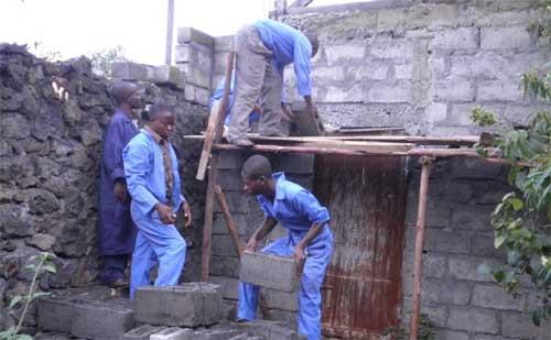 Apprentissage de la construction d'un mur par les jeunes menuisiers dans leur formation de maçonnerie à Goma
