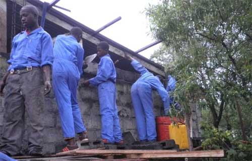 Apprentissage de l'élévation d'un mur par les jeunes menuisiers dans leur formation de maçonnerie à Goma