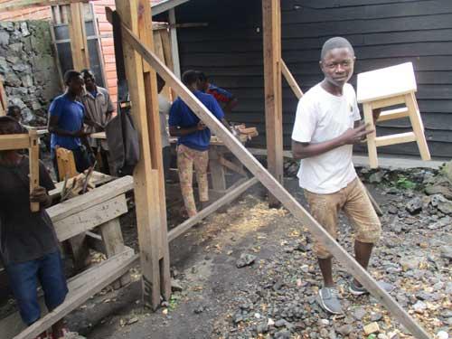 Fabrication d'un tabouret par un enfant soldat démobilisé en formation de menuiserie à Goma
