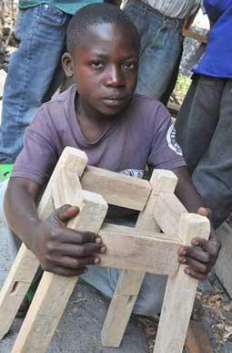 Muhindo présente le tabouret qu'il vient de fabriquer s'entraînant au rabot
