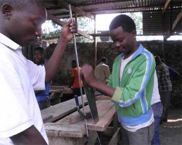Premiers essais du travail à la scie pour les apprentis menuisiers de Goma