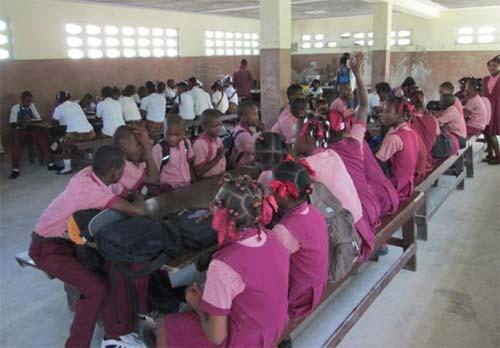 Les enfants attablés à la cantine de l'école St Alphonse Cité Soleil en Haïti