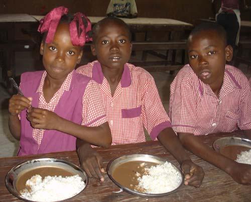 Les enfants sont heureux de prendre un bon repas chaud à la cantine scolaire à l'école St Alphonse de Cité Soleil en Haïti