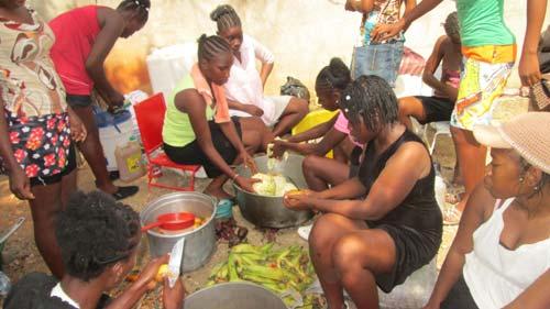 Les cuisinières de l'école préparent le repas sur une plage d'Haïti