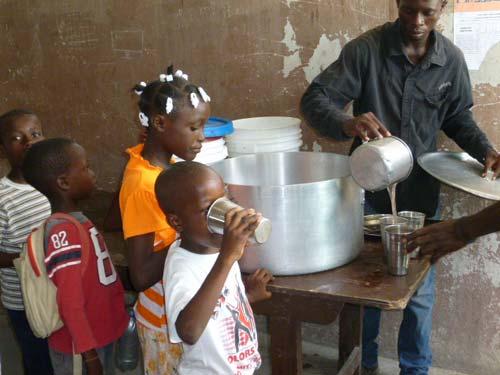 Distribution d'une boisson sucrée durant le club d'été à l'école St Alphonse, bidonville de Cité Soleil en Haïti