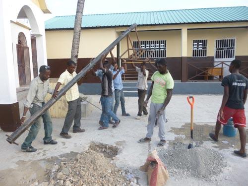 Installation d'un panneau de basket dans la cour de l'école de Cité Soleil en Haïti