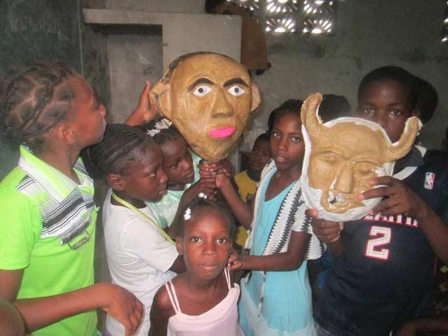 Fabrication de masques en papier mâché durant le club d'été à l'école St Alphonse, bidonville de Cité Soleil en Haïti
