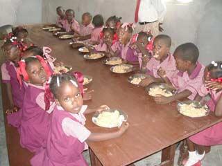 Repas des enfants à la cantine de l'école St Alphonse, bidonville de Cité Soleil, Haïti