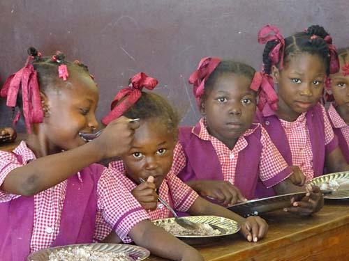 Les enfants du bidonville de Cité Soleil sont heureux de trouver un repas chaud à la cantine de l'école St Alphonse en Haïti