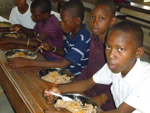 Un repas chaud est servi à midi durant le club d'été à l'école St Alphonse, bidonville de Cité Soleil en Haïti