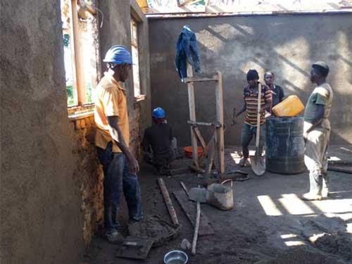 Les maçons terminent le crépi intérieur de l'école de Visiki en RDC
