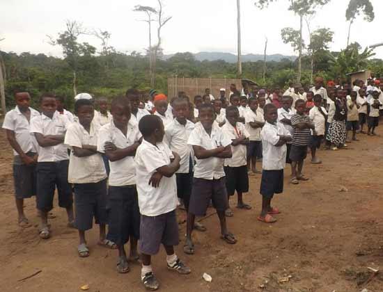 Elèves en rangs dans la cour de la nouvelle école du Village Orange de Kabweke, Nord Kivu en RD Congo