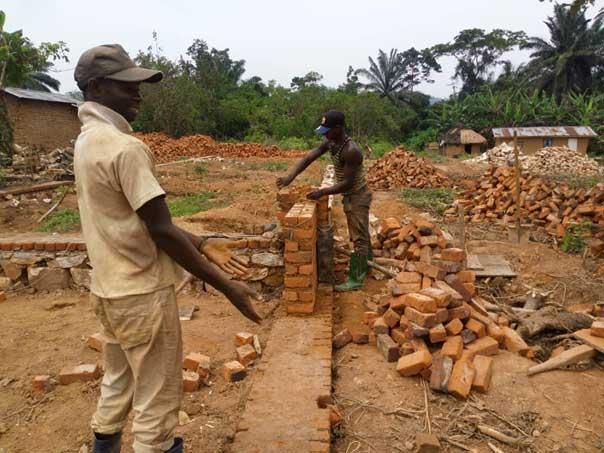 Les maçons posent les premières briques de l'école de Visiki en RDC