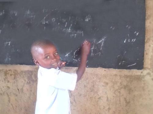 Elève de l'école primaire de Visiki en RD Congo écrivant au tableau noir.
