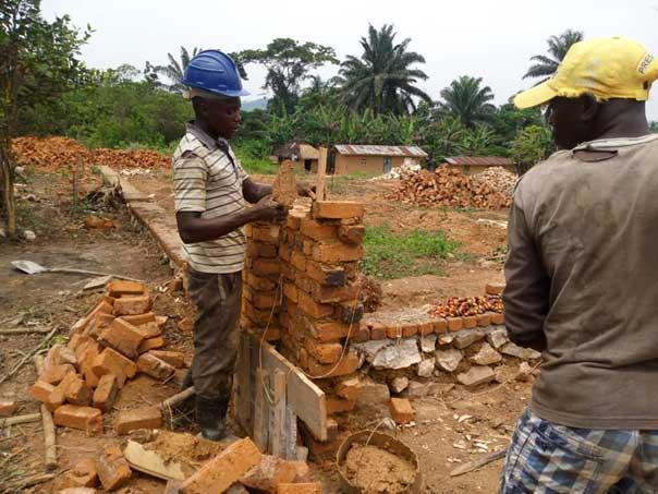 Les maçons empilent les briques pour préparer l'élévation des murs de l'école de Visiki en RDC