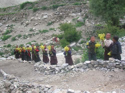 Les enfants de Ting Kyu dans le Haut Dolpo vous accueillent au Népal avec des bouquets de fleurs
