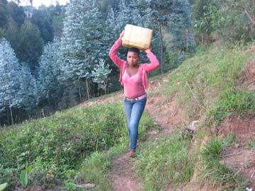 Corvée d'eau au Rwanda : Assumpta porte son bidon d'eau sur la tête