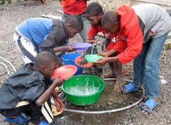 Après le repas, les enfants des rues participent au nettoyage et à la vaisselle