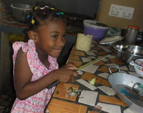 Orpheline de Madagascar aidant à la cuisine pour le repas de Pâques