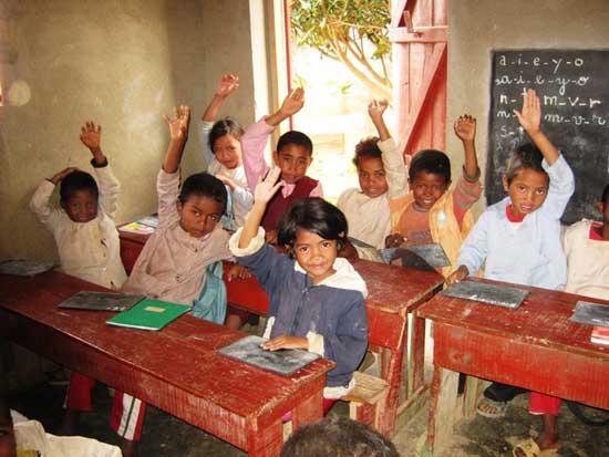 Les élèves lèvent le doigt pour répondre dans leur école de Madagascar