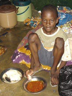 Repas de midi d'un orphelin du sida au Bénin, chez lui à la maison