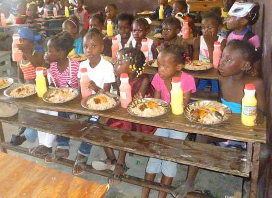 Repas de fête pour célébrer le Carnaval à l'école St Alphonse, bidonville de Cité Soleil en Haïti
