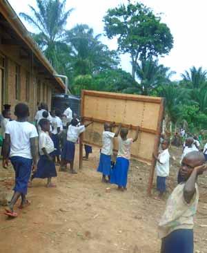 Les élèves installent eux-mêmes les tableaux noirs dans leur classe à l'école Kabweke au Nord Kivu en RD Congo