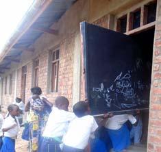 Les élèves installent eux-mêmes les tableaux noirs dans leur classe à l'école Kabweke, village de brousse du Nord Kivu en RD Congo