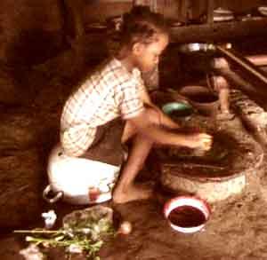 les femmes pilent le manioc sur une pierre à moudre