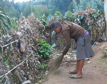>Jeune orpheline balayant la cour de son habitation au Rwanda