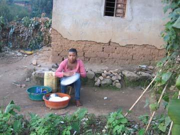 Nettoyage de la vaisselle au Rwanda : Assumpta lave les assiettes et la marmite dans une bassine assise dans la cour