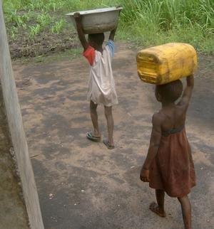 Adduction d'eau au Togo, deux enfants s'en retournent de la  borne fontaine à Badja, Togo